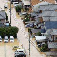 Man the pumps: A neighborhood in Uji, Kyoto Prefecture, is inundated  Tuesday morning. Other areas in the Kinki region also suffered record rainfalls.   KYODO