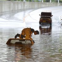 Done driving: A man looks into his flooded car  Tuesday in Neyagawa, Osaka Prefecture.   KYODO