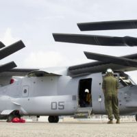 Folded up: An MV-22 Osprey aircraft sits by a hangar at U.S. Marine Corps Air Station Iwakuni in Yamaguchi Prefecture in July. | U.S. MARINE CORPS / KYODO