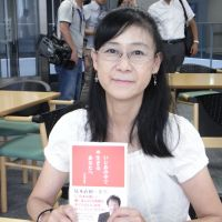 Fighting on: Midori Komori, 55, holds her recently published book on bullying in Tokyo on July 25. | MIZUHO AOKI