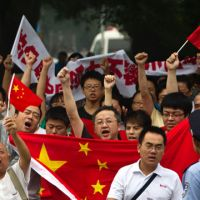 Seeing red: Protesters chanting anti-Japan slogans and carrying Chinese national flags and banners march toward the Japanese Embassy in Beijing on Saturday.   AP
