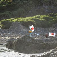 Marking the territory: Japanese nationalists raise Hinomaru flags on an islet at the heart of a territorial row with China on Sunday. No one was reportedly arrested over the incident. | KYODO