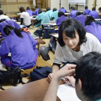 Extra help: Aya Kawai deals with questions from a junior high school student at a tutorial class in the town of Otsuchi, Iwate Prefecture, on July 2. | KYODO