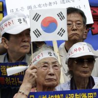 Color of discontent: Korea Liberation Association members take part in an anti-Japan rally outside the Japanese Embassy in Seoul on Thursday. The banner reads: 'Demand an apology and compensation for the wartime sex slaves from the Japanese government.' | AP