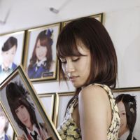 Wall of fame: Atsuko Maeda holds a photo of herself taken from the wall of the AKB48  Theater in  Tokyo after her last performance as a member of the popular all-girl pop group AKB48 on Monday. | AKS / KYODO