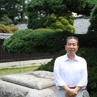 Time-honored: Genuemon Sudo, president of Japan's oldest sake maker, Sudohonke Inc., stands in front of a well near his brewery in Kasama, Ibaraki Prefecture, on Aug. 2.  The well was dug hundreds of years ago. | JUN HONGO