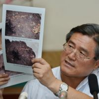Japanese graves: Jo Hui Sung, director of the Institute of History at the Academy of Social Sciences of North Korea, displays photos of what are apparently Japanese graves during an interview  Wednesday in Pyongyang. | KYODO