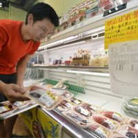 Vote of support: Octopus caught off the coast of Fukushima Prefecture are displayed in a supermarket in the Ueno district in  Tokyo on Aug. 2. The sign hanging from the shelf voices support for Fukushima produce and includes a test result indicating the seafood on display has no detectable radioactive cesium. | KYODO