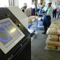 Keeping a close watch: Officials on Sept. 12 check bags of rice for radiation in the town of Aizubange, Fukushima Prefecture. The circle on the screen indicates that no radioactive materials were detected. | KYODO