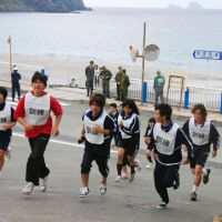 Practicing safety: High school students run toward higher ground during a disaster drill conducted on Kozu Island, 180 km south of Tokyo, on Thursday. | KYODO