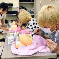 Don't blink: Students at Kubota Beauty and Hairdressing College in Nakano Ward, Tokyo, learn how to apply semipermanent eyelashes. | KYODO
