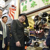 Just fits: Prime Minister Yoshihiko Noda tries on a hat Saturday during a visit to Fukuoka's Kawabata shopping district. | KYODO