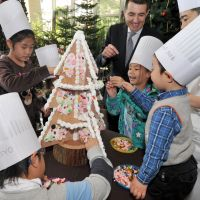 Visions of sugarplums: Children from the Tohoku region and Nishimachi International School in Tokyo decorate a Christmas tree with sweets Wednesday at the Grand Hyatt Tokyo in Minato Ward. | YOSHIAKI MIURA