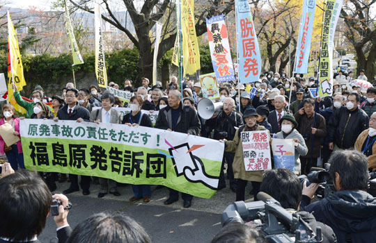 Radiation accountability: Plaintiffs hold a banner Thursday outside the Fukushima prosecutor's office demanding a criminal investigation into Tokyo Electric Power Co. and the government. | KYODO