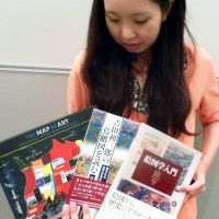 Global explorer: Hanae Watanabe, a Waseda University student, shows her favorite books on maps and graphics during a symposium in June in Yokohama. | KYODO