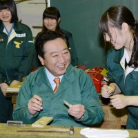 And they're off: A student at Tokyo Metropolitan Kogei High School teaches Prime Minister Yoshihiko Noda how to make a cellphone strap Saturday in Bunkyo Ward as jockeying for the Dec. 16 Lower House election kicked off.   KYODO