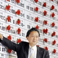 Rosy times: Yukio Hatoyama pins a victory rose on the list of Democratic Party of Japan candidates at campaign headquarters in Tokyo on Aug. 30, 2009, as the DPJ swept to power. | AFP-JIJI
