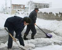 Snow problem: Residents remove snow from a roadside in Noboribetsu, Hokkaido, on Tuesday after snowstorms and strong winds hit wide swaths of northern Japan, disrupting transportation and causing blackouts. | KYODO