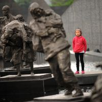 Another generation remembers: A girl walks between bronze sculptures depicting victims of the Nanjing Massacre at the Memorial Museum in the city in May.  The museum marked the 75th anniversary of the slaughter  Thursday. | AFP-JIJI