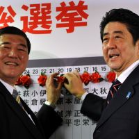 Incoming: Liberal Democratic Party chief Shinzo Abe (right) and the party's secretary general, Shigeru Ishiba, pose in front of a board listing the names of winning candidates in Sunday's Lower House election at the LDP's Tokyo headquarters. | YOSHIAKI MIURA