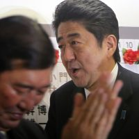 Dynamic duo: Liberal Democratic Party leader Shinzo Abe (right) joins LDP Secretary General Shigeru Ishiba at party headquarters Sunday. | AP