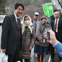 Making an appearance: Prime Minister Shinzo Abe smiles during a visit with residents of Kawauchi, Fukushima Prefecture, on Saturday. | POOL / KYODO