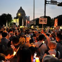 Atom antis: Protesters hold lit candles and placards as they take part in a rally in front of the Diet building to demonstrate against the use of nuclear power on July 29. | AFP-JIJI
