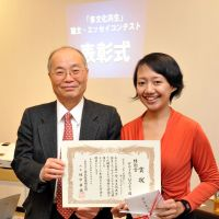 Medical citation: Indonesian nurse Dewi Rachmawati poses for a photo with Hidenori Sakamaki, head of the Japan Immigration Policy Institute, after being presented with a special prize on Dec. 18 in Tokyo for an essay she wrote about her struggles to become a nurse in Japan. | YOSHIAKI MIURA