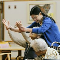 Foreign aid: Gina Konishi gets on-the-job training to become a caregiver at Shofuen, a nursing home for visually impaired elderly, in Ofunato, Iwate Prefecture, on Nov. 6.   KYODO