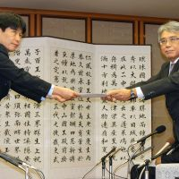 To-do list: Ichita Yamamoto (left), the state minister overseeing Okinawa affairs, receives a set of local development proposals Saturday from Okinawa Vice Gov. Yoshiyuki Uehara. | KYODO