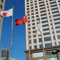 Unfettered: The flags of Japan and China fly side by side in the city of Dalian, Liaoning Province, on Dec. 31. | AFP-JIJI