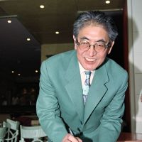 Movie director Nagisa Oshima signs a cast of his hands during the Ninth International Festival of Audio-Visual Programs in January 1994 in Cannes, France. Oshima died Tuesday at the age of 80. | AFP-JIJI