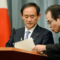 Staying on message: Chief Cabinet Secretary Yoshihide Suga (left) confers with an aide during a news conference Friday after the Cabinet met on the Algerian hostage crisis. | AFP-JIJI