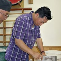 Cutting edge: Gaylong, a Bhutanese farm official, cuts up 'soba' noodles in Hachinohe, Aomori Prefecture, in August. | KYODO