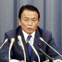 Aso faces reporters Dec. 27 at the Finance Ministry after being named the new minister. | KYODO