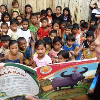 Sharing the fun: Children of the Manobo tribe in Mindanao in the Philippines listen Jan. 5 to a story read by a young student on a scholarship provided by a Japanese sponsor through the Mindanao Children's Library Foundation. | KYODO
