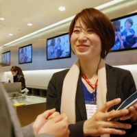 Here to help: Yuki Obataya, one of nearly 20 'concierges' employed at the Uniqlo clothing chain's flagship store in Tokyo's Ginza district, helps a customer last month. | KYODO