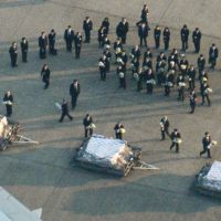 Government officials and JGC Corp employees place flowers on caskets brought by plane to Tokyo's Haneda airport Friday. | KYODO