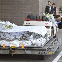 Grim task: JGC Corp. President Koichi Kawana (right) prepares to lay flowers on the coffin of Tadanori Aratani, an official of the company killed during last week's Algerian hostage crisis, after a plane carrying his body arrived at Narita airport Saturday. | KYODO