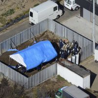 Grisly find: Police go over a lot in Kuki, Saitama Prefecture, where Makoto Shimomi was found slain Tuesday along with a murdered woman believed to be his wife, Mie. | KYODO