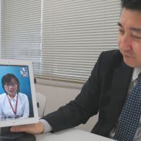 Making life easier: Hironobu Murai, director of Rsystem Co., demonstrates the firm's Tel Tell Concierge video-call translation service at its Tokyo office Jan. 16. | KAZUAKI NAGATA