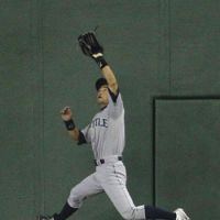 Good timing: Mariners outfielder Ichiro Suzuki catches a flyball hit by Athletics catcher Kurt Suzuki in the fifth inning of Thursday's game at Tokyo Dome. Oakland won the series finale 4-1. | KYODO