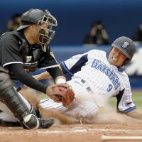 Slide rule: Yokohama's Ikki Shimamura is tagged out by Hanshin catcher Taichi Okazaki during the BayStars' 4-3 win on Saturday. | KYODO