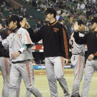 That winning feeling: Yomiuri Giants pitcher D.J. Houlton (54) and his teammates celebrate their 5-2 victory over the Seibu Lions on Tuesday. | KYODO