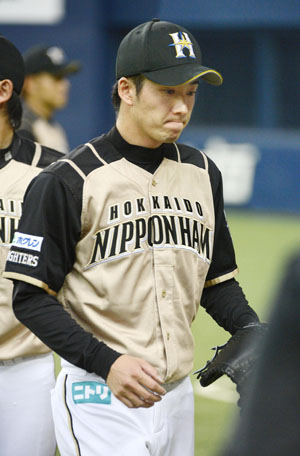 Not my day: Hokkaido Nippon Ham pitcher Yuki Saito returns to the bench after the first inning of the Fighters' 7-6 loss to the Buffaloes on Sunday. | KYODO
