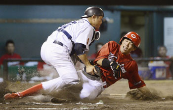 Close contact: Hiroshima's Soichiro Amaya is tagged out by Chunichi catcher Motonobu Tanishige during the Dragons' 4-2 win on Tuesday. | KYODO