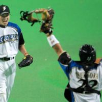Time to celebrate: Fighters catcher Shinya Tsuruoka and closer Hisashi Takeda show their excitement after the final out. | KYODO