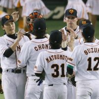 Getting the job done: The Yomiuri Giants congratulate each other after an 8-1 victory over the Hokkaido Nippon Ham Fighters in Game 1 of the Japan Series on Saturday at Tokyo Dome. | KYODO