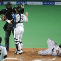 Major controversy: Fighters catcher Shinya Tsuruoka speaks to home plate umpire Koichi Yanada after Giants batter Ken Kato fell to the ground after a pitch in the fourth inning of Game 4 of the Japan Series on Thursday. Hokkaido Nippon Ham pitcher Kazahito Tadano was ejected after Tsuruoka ruled he had hit Kato, but replays showed otherwise. | KYODO