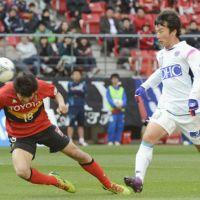 Lone goal: Grampus' Kensuke Nagai (left) scores with a header in the 27th minute as Sagan's Kim Min Woo looks on in Nagoya's 1-0 win over Tosu at Toyota Stadium on Saturday. | KYODO